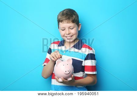 Portrait of young boy with piggy bank on blue background