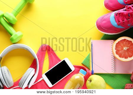 Fitness equipment with smartphone on yellow background