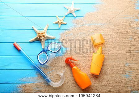 Sunscreen with diving snorkel mask and starfish on wooden table