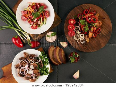 Three dishes stand on dark stone background. Fresh low-calories salad healthy snack main course. Ingredients mushroom tomato onion carrot garlic pepper chicken breast greens spices. Top view