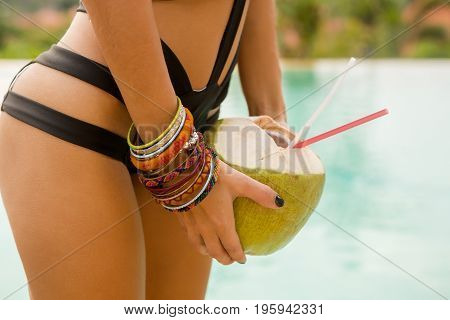 Close up of thirsty sexy fit woman in black sensual swimsuit hold open cool coconut in hand with lot of bracelet wristband. Outdoor lifestyle photo of cute girl on a hot sunny summer day.