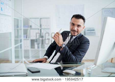 Portrait of handsome confident Turkish businessman with pen in his hand