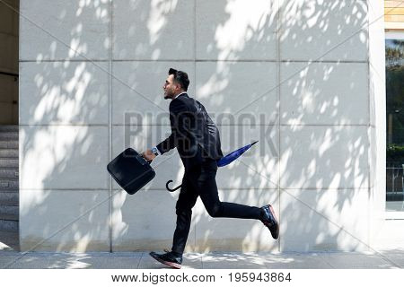 Businessman running with briefcase and umbrella in his hands