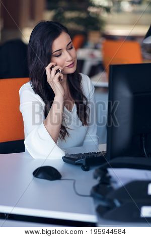 Beautiful young woman working on computer and talking on phone.