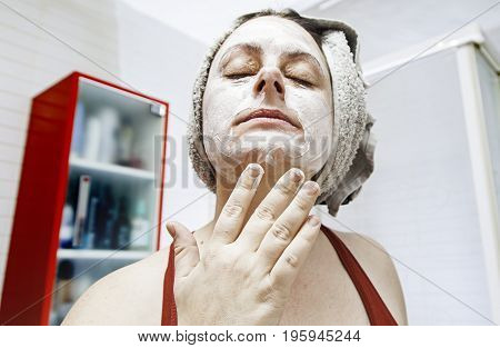Young woman putting on facial creams detail of beauty and body care