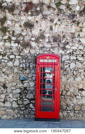 Red Phone Booth on Stone Wall in Gibraltar