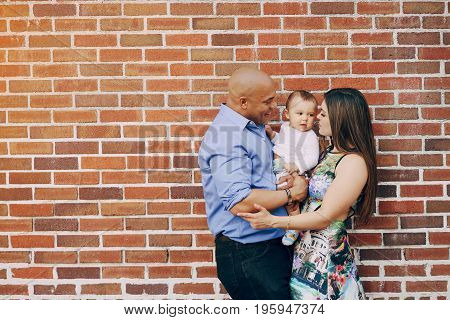 mom and dad a wonderful little son near wall in summer sunny city
