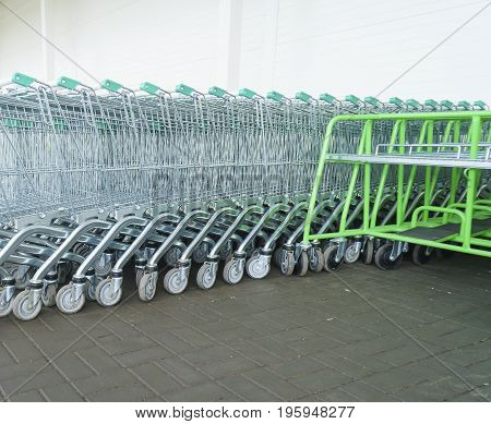 Many green empty Shopping carts on a parking lot