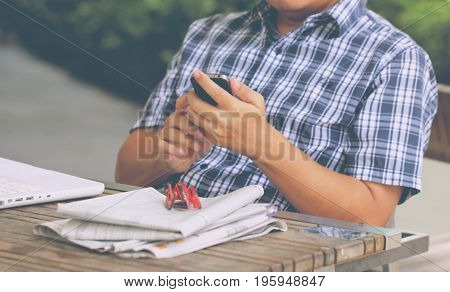 Asian Man's Hand Touching Smart Phone With White Laptop.
