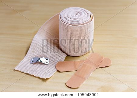 Closeup of medical elastic bandage on wood table.
