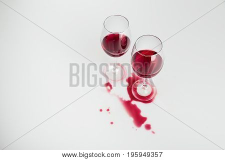 Close-up View Of Red Wine In Glasses And Spilled Out Isolated On White