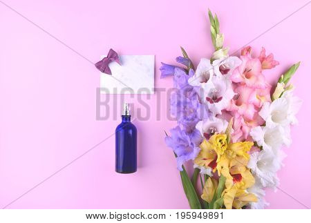 Fragrant perfume with beautiful gladiolus flowers on trendy background. Place for your text.