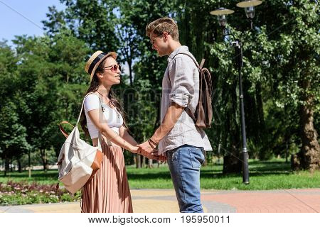 Smiling Multicultural Couple Holding Hands And Looking At Each Other In Park