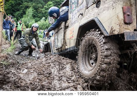 LUBOTIN UKRAINE - JULY 23 2016: RFC Ukraine Wild Boar Challenge 2016. Team on Uaz 469 setting a recovery sand tracks to overcome a hard pit.