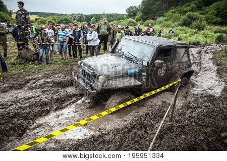 LUBOTIN UKRAINE - JULY 23 2016: RFC Ukraine Wild Boar Challenge 2016. The participant on Jeep passes a deep muddy pit.