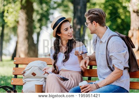 Happy Multicultural Couple Having Conversation While Sitting On Bench