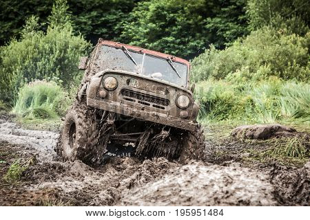 LUBOTIN UKRAINE - JULY 23 2016: RFC Ukraine Wild Boar Challenge 2016. Custom built Off-road Trophy UAZ 469 passing mud pit.