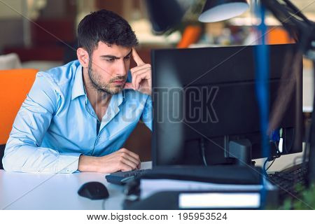 Freelance young programmer working in startup office.