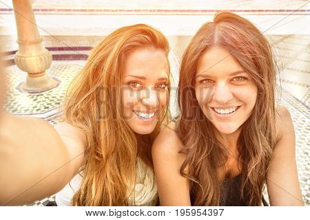 Young best friends couple taking a funny selfie in outdoors museum. Cheerful girls laugh enjoying best moments during a excursion around city trip. Travel girlfriends having emotional fun together.
