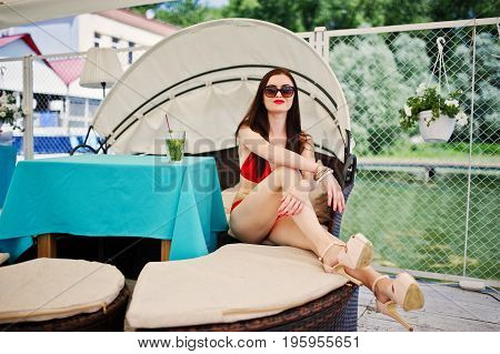 Portrait Of A Stunning Girl In Red Bikini Swimsuit And Sunglasses Enjoying Her Time By Sitting On Th
