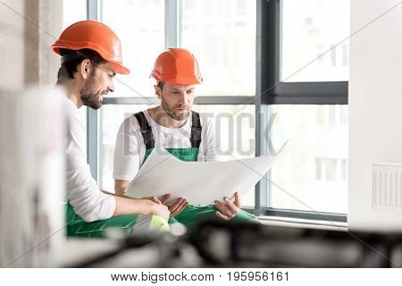 Side view bearded constructor demonstrating happiness while sitting near serious comrade. Serene man looking through blueprint