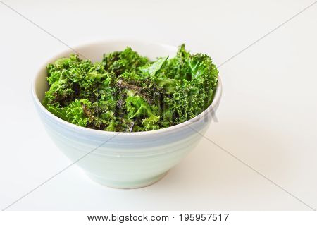 Kale chips and fresh kale leaves with oil in blue bowl on white background. Kale salad