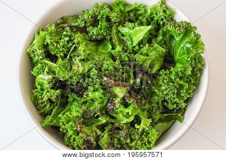 Kale salad in big bowl on white table. Fresh oily kale leaves. Healthy food