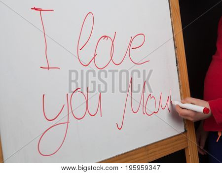 Words I love you Mom writeen on whiteboard with childs hand holding whiteboard marker