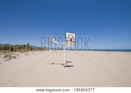 basketball and soccer courts on sand at Beach of PIne or Pinar in Grao of Castellon Valencia Spain Europe. Blue clear sky Mediterranean Sea and Benicassim in the horizon