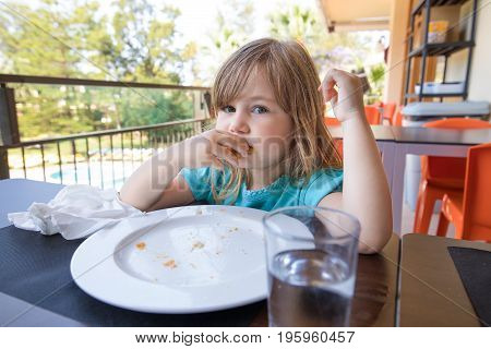 Little Child Eating At Terrace Of Restaurant