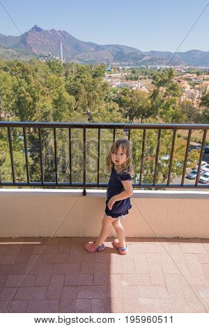 three years old blonde child with blue dress looking surprised expression at terrace of house with city and mountain horizon view
