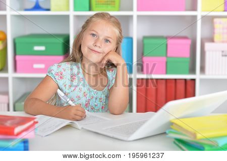 Cute girl sitting at table with laptop and doing homework