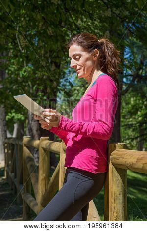 Side View Woman Leaning In Wooden Fence Watching Tablet
