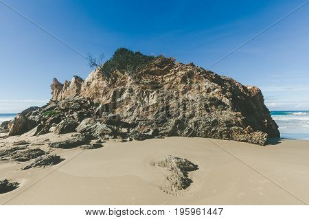 Eroded rock formation on sandy ocean beach at high noon casting long shadows with copy space