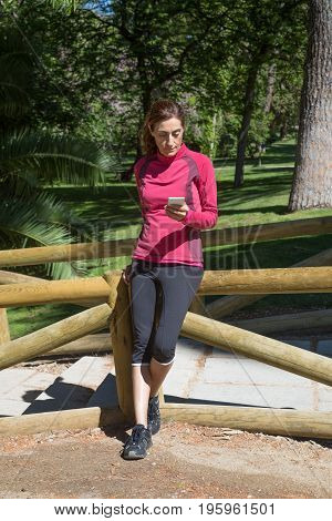 Sporty Woman Leaning In Wooden Railing Using Mobile
