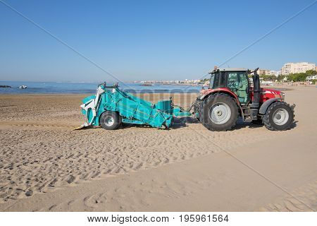 red tractor with green trailer cleaner cleaning sand of Beach Els Terrers in Benicassim Castellon Valencia Spain Europe. Mediterranean Sea