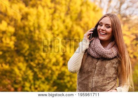 Technology and communication. Attractive fashionable woman talking on mobile phone outdoor walking in autumnal park