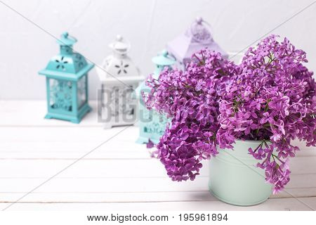 Flowers composition. Lilac flowers and brigh lanterns on white wooden background against grey wall. Selective focus. Place for text.