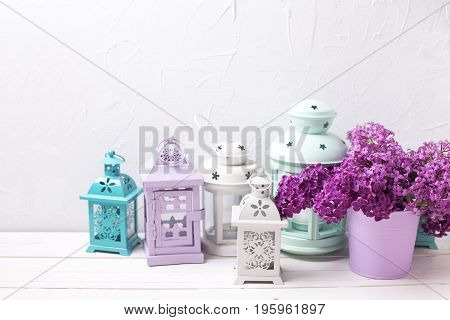 Flower composition. Lilac flowers and brigh lanterns on white wooden background against grey wall. Selective focus. Place for text.