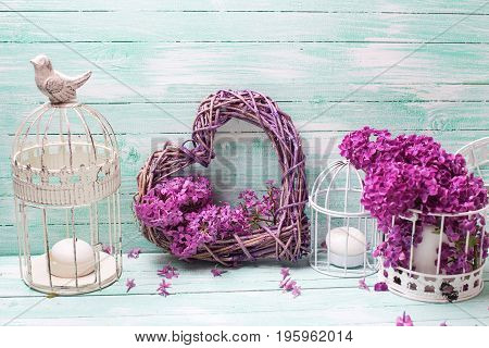 Violet lilac flowers lanterns and heart on turquoise wooden background. Selective focus. Place for text.