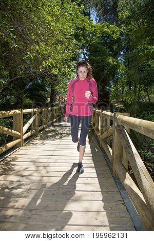 Woman Running On Wooden Footbridge In Park
