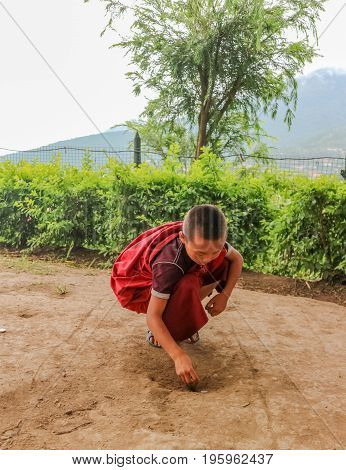 Thimphu Bhutan - September 15 2016: Young Bhutanese monk putting coins on the soil in a monastery in Bhutan South Asia