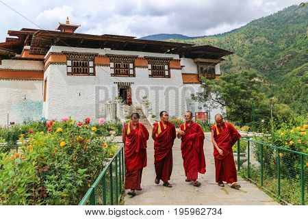 Thimphu Bhutan - September 15 2016: Four monks walking in the garden of Simtokha Dzong Thimphu Bhutan South Asia