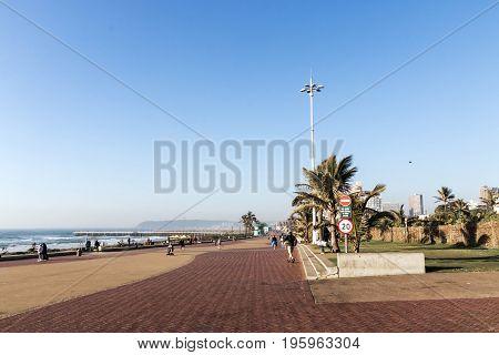 Many Pedestrians On Paved Beachfront Promenade