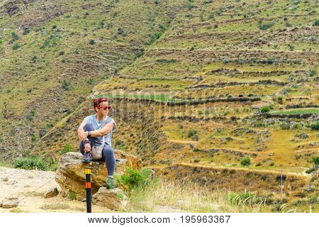 Thimphu, Bhutan - September 16, 2016: Caucasian Woman Sitting On A Rock And Enjoying The Scenery Of