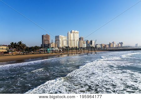 DURBAN SOUTH AFRICA - JULY 7 2017: Early morning view of waves breaking on beach against blue Durban city skyline in South Africa