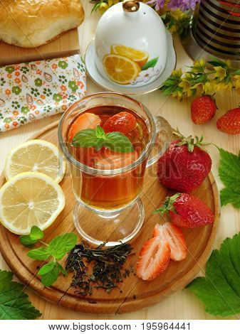 Herbal tea with herbs, lemon and strawberries in a glass for breakfast on a wooden background