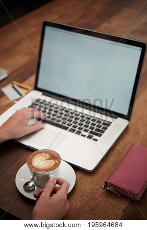 Woman having cup of cappuccino when starting to work on laptop