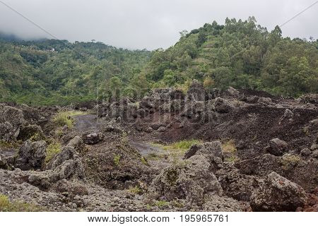 View of a valley with dark ground and some buildings far away on the hill forest. Foggy landscape in Bali, Indonesia