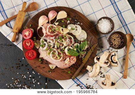 Cooking fresh chicken fillet with fresh vegetables and spices seasoning on rustic wooden board. The table with the ingredients for the dishes. Dark stone background. Healthy low-calories food.